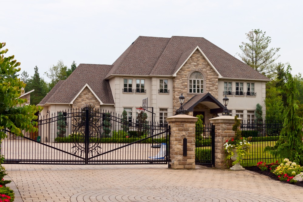 Large home with black ornamental iron driveway gate and fencing