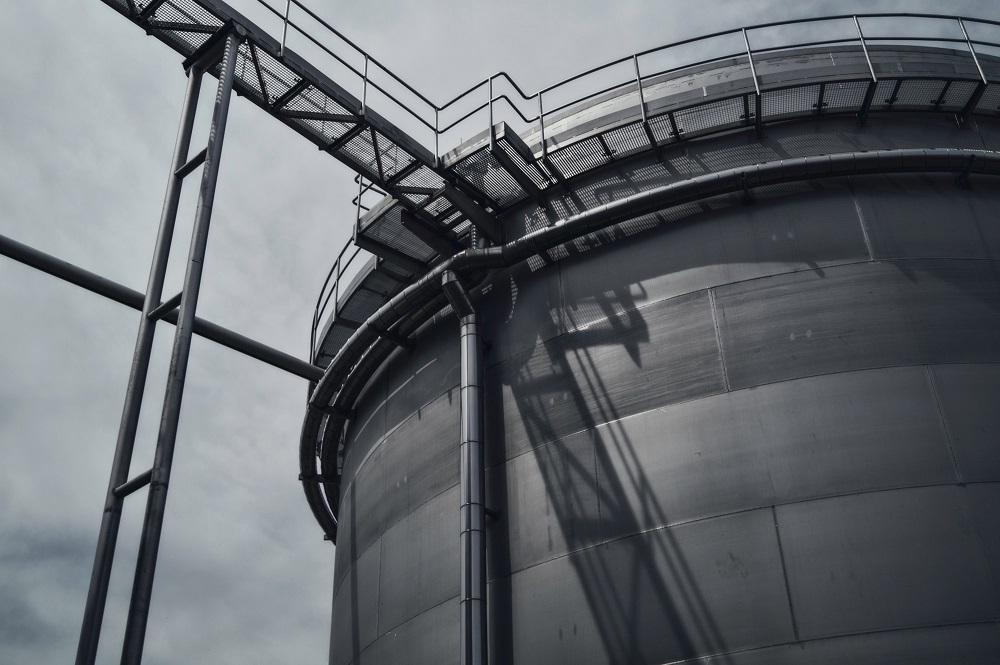 Large industrial holding tank made entirely of metal with walkway and ladder