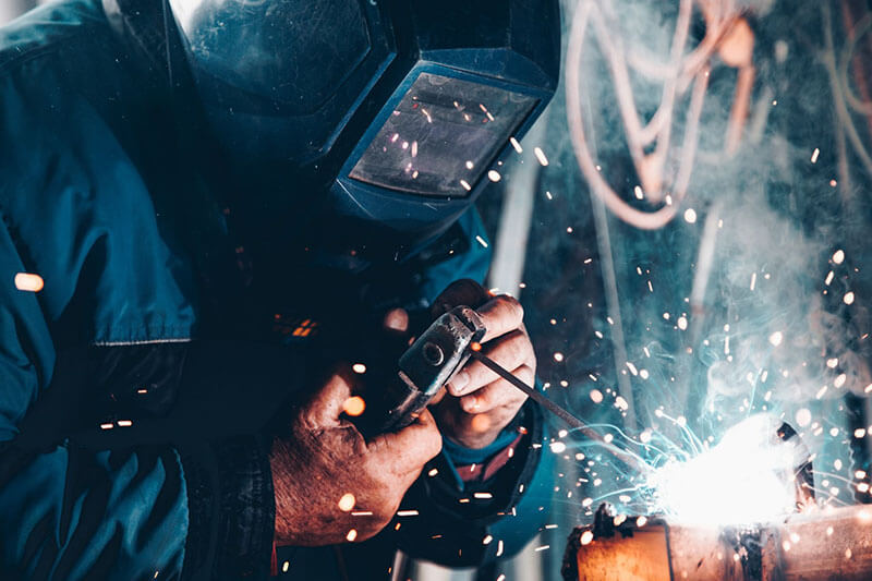 Welder at work with full protective head gear
